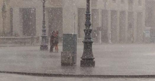 Lecce, il bacio degli innamorati in piazza Sant'Oronzo durante il temporale FOTO